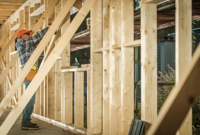 Wooden House Construction Job. Contractor Carpenter Finishing Building wood Beams Frame. Industrial Theme.