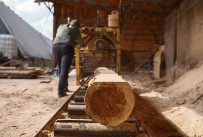 Joiner works on woodworking machine, lumber industry, carpentry. Wood processing on factory, forest sawing in lumberyard, lumbering