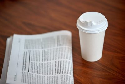 coffee drink in paper cup and newspaper on table